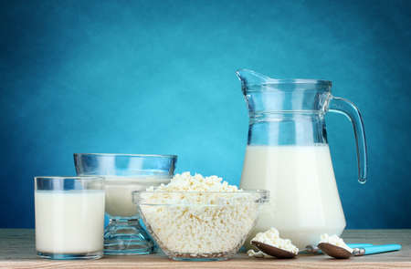 Dairy products on wooden table on blue background photo