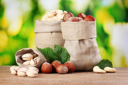 many nuts in bags on green background Stock Photo - 11290985