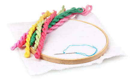 thread count: The embroidery hoop with canvas and bright sewing threads for embroidery isolated on white