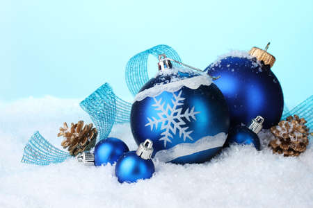 beautiful blue Christmas balls and cones in snow on blue background photo