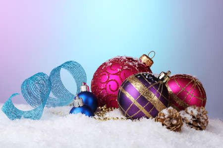 beautiful Christmas balls and cones on snow on bright background photo