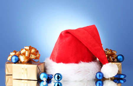 Beautiful Christmas hat, gifts and Christmas balls on blue  background photo