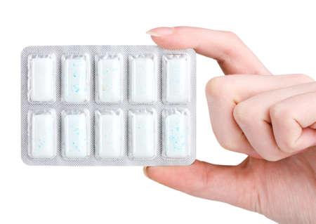 goma de mascar: Blister con 10 gomas de mascar en la mano aislados en blanco