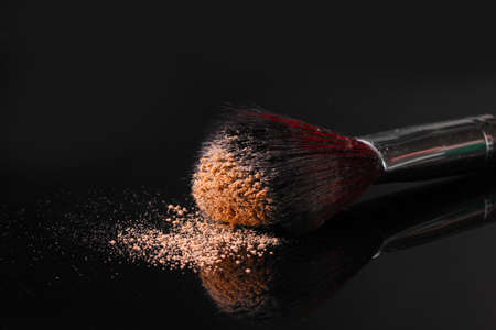 makeup a brush: Make up brush with powder isolated on black