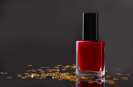 Red nail polish on black background photo