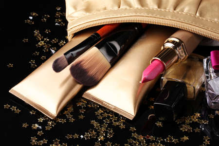 Beautiful golden makeup bag and cosmetics isolated on black Stock Photo - 11291202