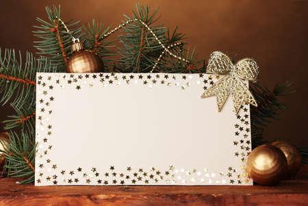 carte postale, boules de Noël et sapin sur la table en bois sur fond brun