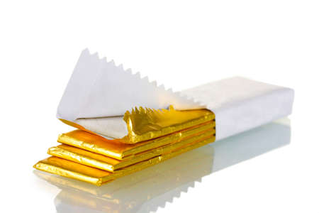 chewing: chewing gums wrapped in golden foil, isolated on white