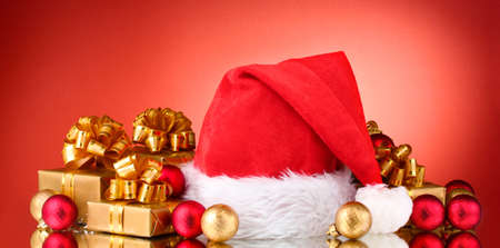 Beautiful Christmas hat, gifts and Christmas balls on red  background Stock Photo - 11337489