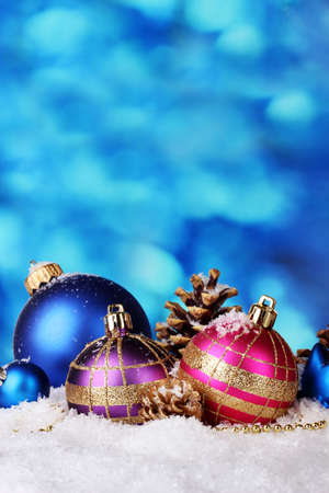 beautiful bright Christmas balls and cones on snow on blue background photo