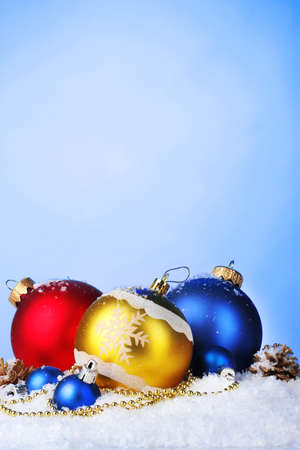 beautiful bright Christmas balls and cones in snow on blue background photo