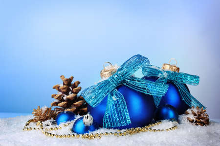 beautiful blue Christmas balls and cones on snow on blue background photo