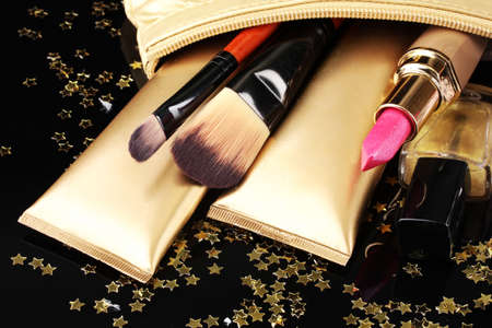 Beautiful golden makeup bag and cosmetics isolated on black photo
