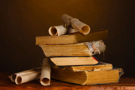 Pile of old books and scroll on brown photo