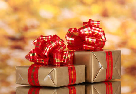 beautiful golden gifts with red ribbon on yellow background Stock Photo - 11337772