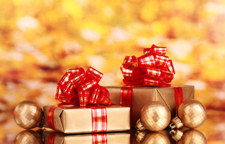 beautiful golden gifts with red ribbon and Christmas balls on yellow background Stock Photo - 11337897