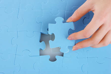 Hand collecting a part of a puzzle Stock Photo - 11337905