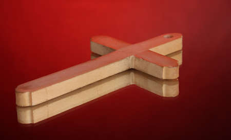 Wooden cross on red background photo