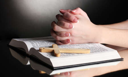 Female hands on open russian holy bible on black backround Stock Photo