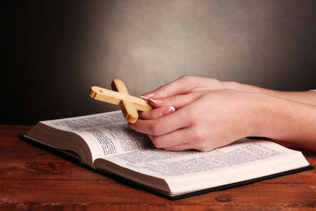 Hands folded in prayer over open russian Holy Bible photo