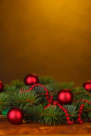Christmas tree with beautiful New Year's balls on wooden table on brown background photo