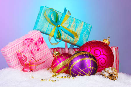 beautiful Christmas balls and gifts on snow on bright background photo