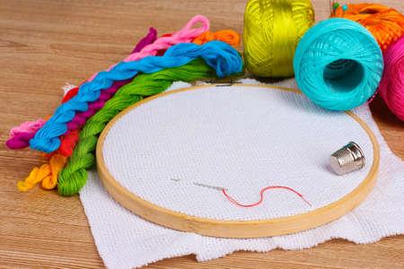 bordados: El bastidor de bordado con una lona y los hilos de coser para el bordado de brillantes en la tabla Foto de archivo
