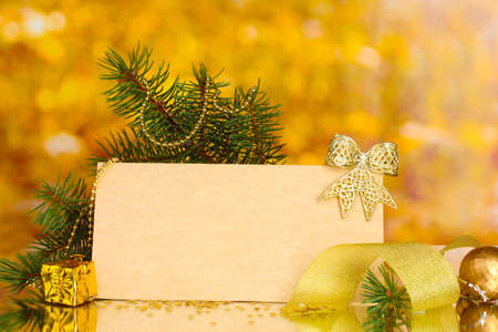 blank postcard, Christmas balls and fir-tree on yellow background photo