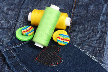 Heart-shaped patch on jeans with threads and buttons closeup photo