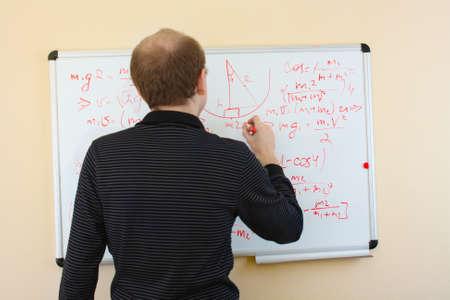 solves: man writing math formulas on a white-board Stock Photo
