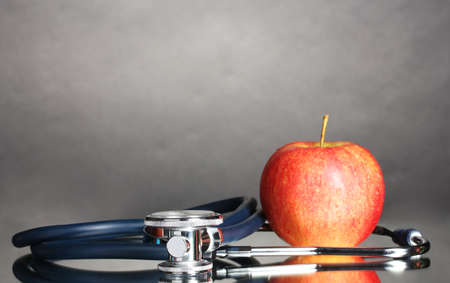 Medical stethoscope and red apple on grey photo