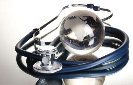 global health: Globe and stethoscope isolated on white