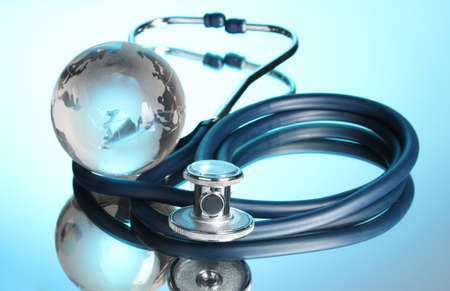 Globe and stethoscope on blue photo