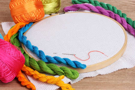 thread count: The embroidery hoop with canvas and bright sewing threads for embroidery in the table