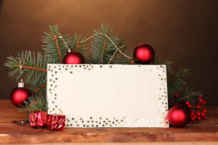 blank postcard, Christmas balls and fir-tree on wooden table on brown background photo