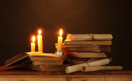 the arts is ancient: Pile of old books with candle and scroll in dark