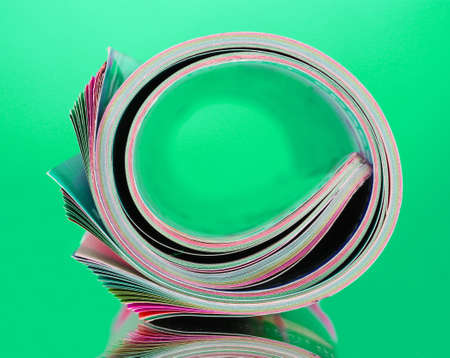 Rolled up magazines on green background photo