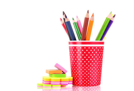 red glass with colorful pencils and stationery isolated on white photo