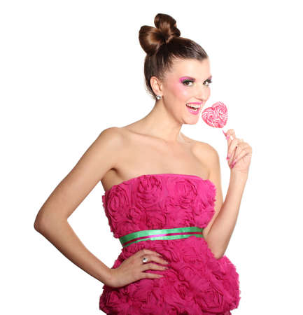 Young girl like a doll in pink dresses with heart-shaped candy  isolated on white Stock Photo - 11490015