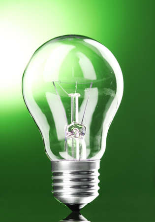 Light bulb on green background photo