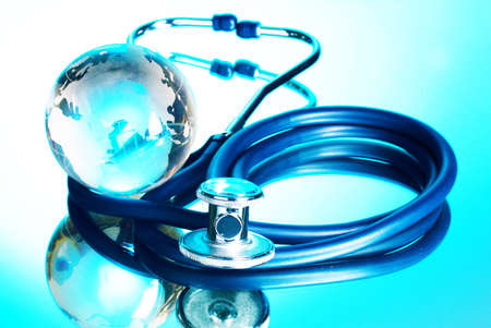 Globe and stethoscope on blue background  photo