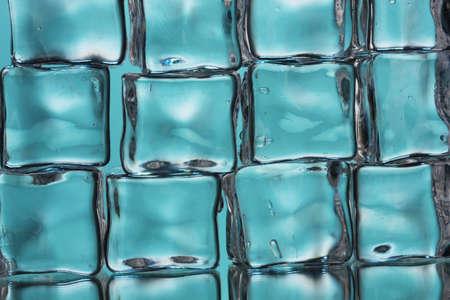 Ice cubes on blue closeup photo