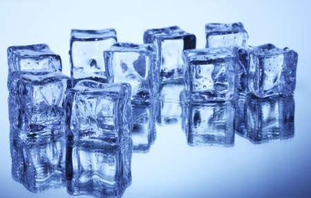 Melting ice cubes on blue background photo