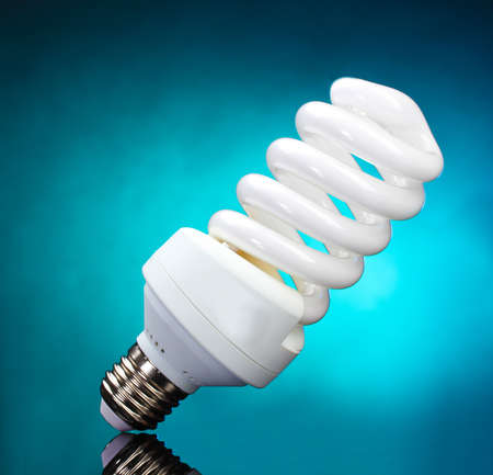 Energy saving lamp on blue background photo