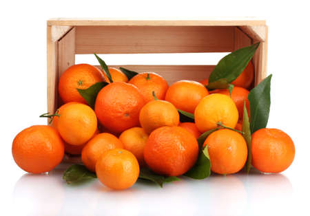 dropped: Ripe tasty tangerines with leaves in wooden box dropped isolated on white Stock Photo