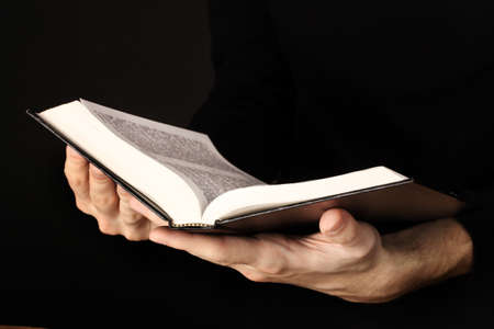 bible open: Hands holding open russian bible on black background