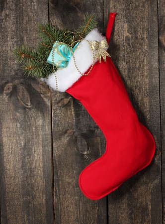 Christmas sock with gifts on wooden background photo