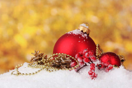 beautiful red Christmas balls and cones on snow on yellow background photo