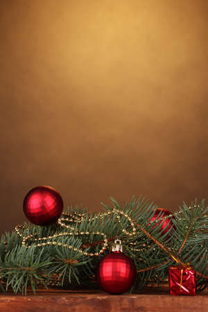 Christmas tree with beautiful New Years balls on wooden table on brown background photo