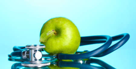 Medical stethoscope and green apple on blue photo